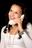 Cute young woman talking on the phone. On black background Stock Photos