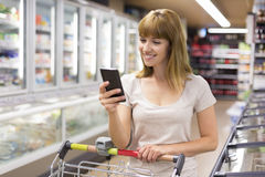 Cute young woman texting on her cell phone in supermarket. Stock Photo