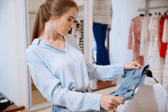 Cute young woman thinking and choosing clothes in clothing shop Stock Photo