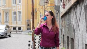 Cute young woman walking along the street and drink coffee stock footage