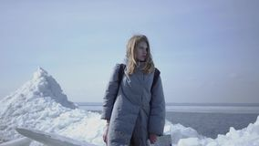 Cute young woman in warm jacket walking on the glacier, holding her cellphone in raised hand, trying to find mobile. Portrait of young blond pretty woman in a stock footage