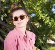 Cute young woman wearing sunglasses outdoors. Pink shirt, hair wrapped. Flowering tree in the background Stock Photography
