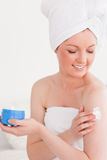 Cute young woman wearing a towel using skin cream Stock Photography