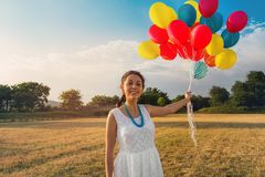 Cute young woman in white dress with balloons in her hands. The concept of freedom and joy. Field on the background.  royalty free stock photos