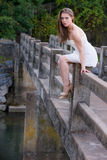 Cute young woman in white dress sitting on side of bridge Stock Image