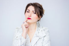 Cute young woman in the white elegant jacket is thinking about something.Woman thinking Stock Images