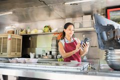 Swiping credit card in a food truck. Cute young woman working in a food truck and swiping a credit card to process a payment Royalty Free Stock Image