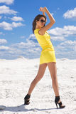 Cute young woman in yellow dress on the snow Stock Images