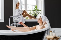 Cute young women dressed in white dressing gowns and towels on the head have fun in the bathroom royalty free stock images