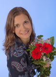Cute young women with flowers over blue backgroung Royalty Free Stock Photos