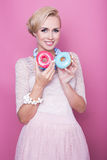Cute young women hold colorful donuts. Soft colors Stock Images