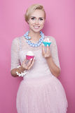 Cute young women hold colorful sweets. Soft colors Royalty Free Stock Image