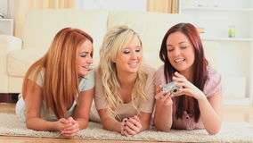Cute young women taking a picture of themselves on the floor Stock Photos