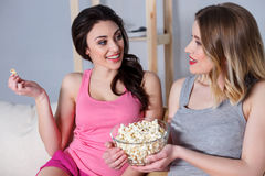 Cute young women watching tv at home. Best friends are talking and smiling. They are sitting on sofa and smiling. Girls are eating popcorn while watching movie Stock Image