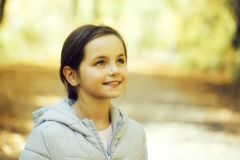 Cute youthful girl. With beautiful eyes and smiling face posing in park on natural background royalty free stock photography