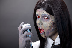 Cute zombie girl with retro microphone Stock Image