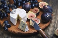 Free Cuted Blue Cheese, Fresh Fig Halfs And Grapes On Rustic Wooden Plate. Moody Scene With Selective Focus Royalty Free Stock Images - 159249779
