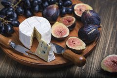 Free Cuted Blue Cheese, Fresh Fig Halfs And Grapes On Rustic Wooden Plate. Moody Scene With Selective Focus Royalty Free Stock Images - 168319539