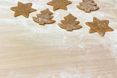 Cuted out shapes of cookies on the floured wooden board Stock Photography