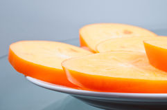 Cuted persimmon few pieces on plate. Close up Royalty Free Stock Image