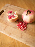 Cuted pomegranates with seeds on wooden board Stock Photo