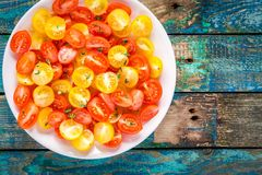 Cuted yellow and red cherry tomatoes in a bowl Stock Image