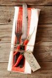 Cutelaria amarrada no guardanapo com Chili Pepper & a etiqueta vermelhos Foto de Stock