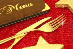 Cutelaria do Natal e menu dourados do restaurante foto de stock