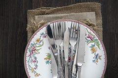 Cutelaria e louça do vintage em panos no backgrou de madeira rústico Imagem de Stock