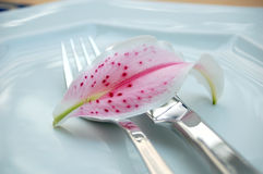 Cutelaria na placa com lilium Fotografia de Stock