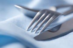 Cutelaria no linho azul Fotografia de Stock