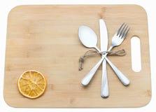 Cutelaria que entrecruza em uma placa de desbastamento de madeira Fundo culinário com placa de corte Foto de Stock Royalty Free