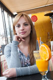 Cutest blond on earth sitting at table in coffee shop Royalty Free Stock Photography