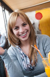 Cutest blond on earth sitting at table in coffee shop Royalty Free Stock Images