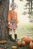 The cutest little girl ever. Little girl wearing adorable children clothing with pumpkins excited for Fall Stock Image