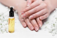 Cuticle oil. Yellow cuticle oil bottle and a female hands on a white wooden table background. Fingernail care concept stock images