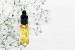 Cuticle oil. Yellow cuticle oil bottle on a white wooden table background. Fingernail care concept stock photo