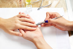 Cuticle pusher tool in nails salon woman hands Royalty Free Stock Images