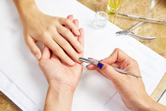 Cuticle pusher tool in nails salon woman hands Royalty Free Stock Photography