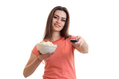 Cutie brunette girl watch a tv with pop-corn and smiles. Isolated on white background Royalty Free Stock Images