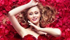 Cutie de sourire parmi des pétales de rose Photo stock