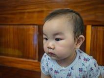 Cutie en de knappe Aziatische jongensbaby of de zuigeling maken een gezicht als geinteresseerd royalty-vrije stock afbeelding