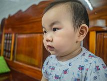 Cutie en de knappe Aziatische jongensbaby of de zuigeling maken een gezicht als geinteresseerd stock afbeelding