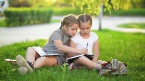 Cutie flickor som tillsammans gör utomhus- läxa De får kunskap afterschool arkivfilmer