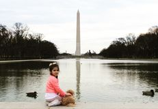 A cutie in front of Lincoln memorial with beautiful view of Washington monument. Lovely day with lovely Little girl and her puppy in Washington, D.C royalty free stock photography