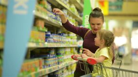 Cutie girl with caucasian appearance is eating lollipop and sitting in supermarket trolley. Mother on background chooses. Baby food for her daughter. Hd stock video