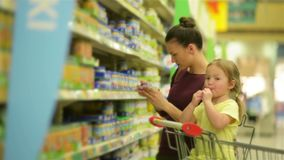 Cutie girl with caucasian appearance is eating lollipop and sitting in supermarket trolley. Mother on background chooses. Baby food for her daughter. HD stock footage