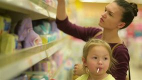 Cutie girl with lollipop sitting in supermarket trolley. Mother on background chooses wet wipes. HD, daughter, family, supermarket shelf stock video
