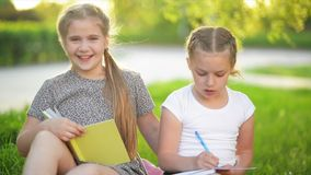 Cutie girls doing homework together outdoor. They are getting knowledge afterschool. Relax, hd, fun, smile stock video