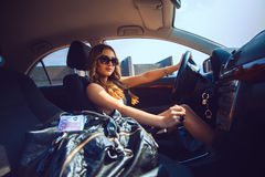 Cutie młoda dziewczyna jedzie nowego samochód z torbą w okularach przeciwsłonecznych folował o Fotografia Stock